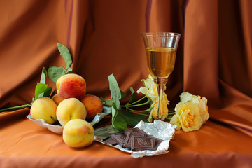 Glass of white wine, peaches, roses and chocolate bar.