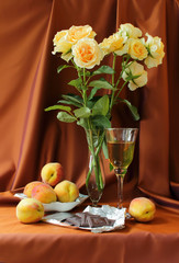 Still life with roses and glass of wine, peaches and chocolate.