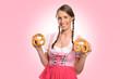 canvas print picture - Hübsche Frau aus Bayern im Dirndl hält zwei Brezel