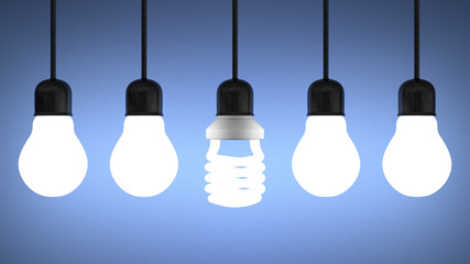 Glowing spiral light bulb hanging among tungsten ones on blue