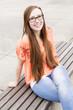 Frau mit langen roten Haaren sitzt auf einer Bank