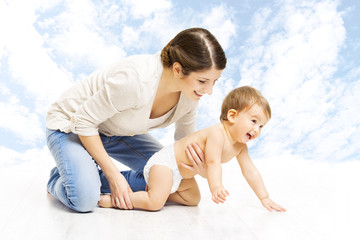 Mother baby happy playing. Child in diaper crawling over sky