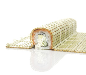Sushi roll in a bamboo mat isolated