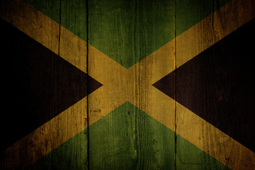An Jamaican flag over a grunge wooden background.
