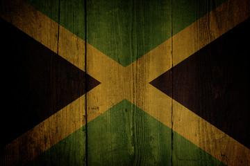 An Jamaican flag over a grunge wooden background.