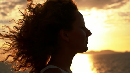 Smiling Woman in Profile Enjoying Sea Breeze against Background