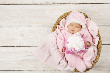 Baby girl with gift sleeping on wooden background, newborn