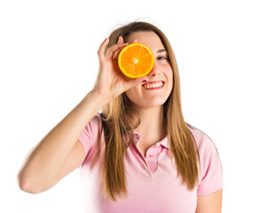 Young girl playing with orange over white background