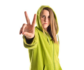 Girl doing victory gesture over white background