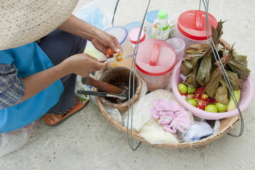 Thai woman cooks a salad on a street on Samet Island, Thailand.