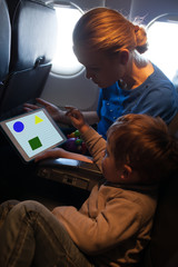 Young mother and son traveling on an aeroplane