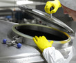 worker in yellow gloves opening industrial process tank