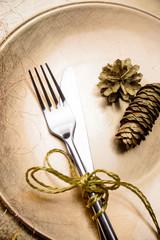 Goldener Teller mit Besteck und Weihnachtsdeko