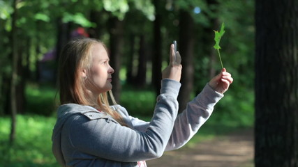 Young woman taking a picture of leaf.