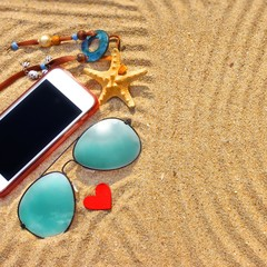Sunglasses and  smartphone on the beach