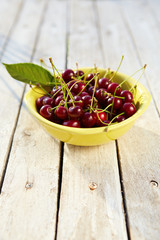 Yellow bowl full of fresh cherries