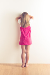 portrait of sad little girl standing near wall