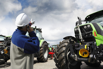 modern farmer in hard-hat and tractors