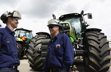 two mechanics standing in front of giant farming tractors