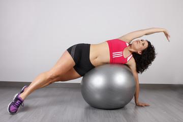 Mujer estirando brazos y cuerpo en el gimnasio.