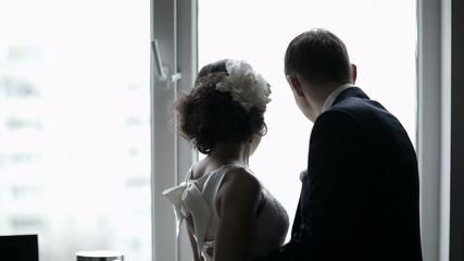 Bridal pair looking out the window.