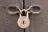 Old rusty padlock on a iron door