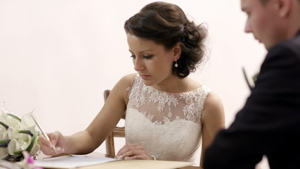 Bride signing marriage license.