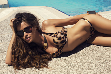 sexy woman  in bikini relaxing beside a swimming pool