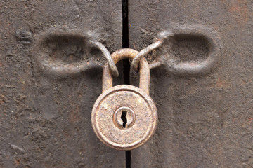 Old rusty padlock on a iron door