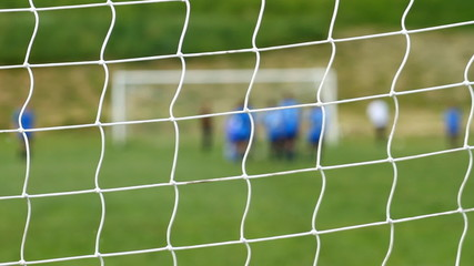 Childrens game of soccer from behind goal net