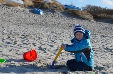 Kind mit Winterkleidung spielt am Strand