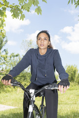 Portrait of woman riding a bike, outdoor.
