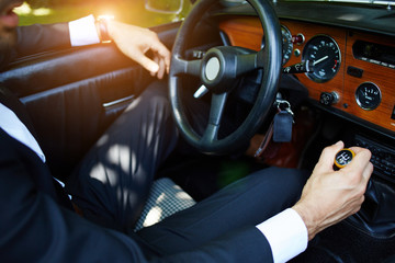 Chauffeur's hands on the steering wheel of cabriolet car