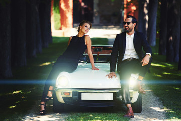 Stylish and rich couple leaning at their classic luxury car