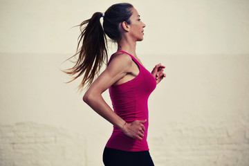 Beautiful sporty woman running with high speed