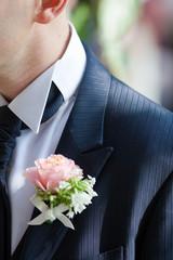 Il dettaglio di un fiore all'occhiello di uno sposo
