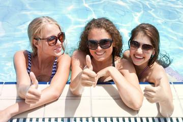 Три красивые девушки у бассейна в очках