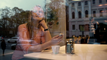Woman with phone in cafe enjoying outside view