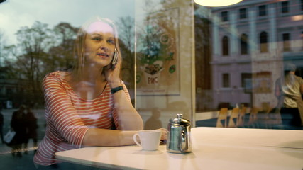 Woman talking on mobile phone in cafe