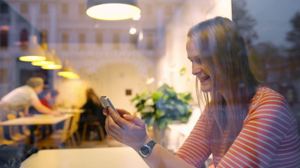 Happy woman in cafe thinking over sms she typing