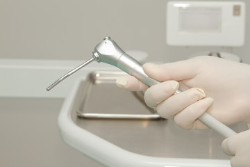 Dentist's hand  holding dental tool in dental clinic
