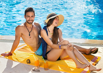 Happy carefree couple relaxing poolside.