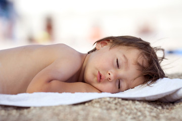 Adorable baby boy, sleeping on the beach