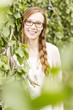 Frau mit roten Haaren und Brille vor natürlichem Hintergrund