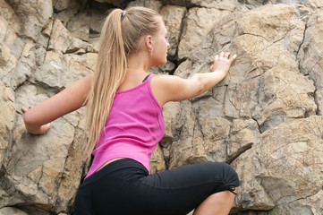Young woman climbing on the rock