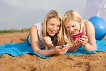 Zwei junge Frauen am Strand mit Smartphone