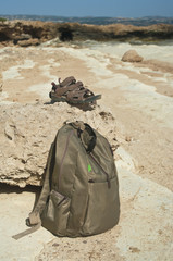 backpack and sandals on rock