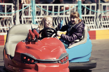 Happy teenage girls driving a bumper cars