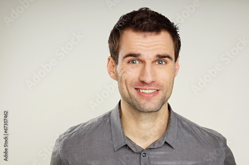 canvas print picture Portrait of a handsome smiling man at grey shirt