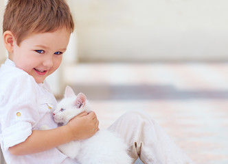 happy kid holding cute white cat